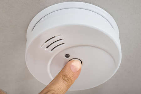 fire safety: Close-up Photo Of Finger Testing Smoke Detector Stock Photo