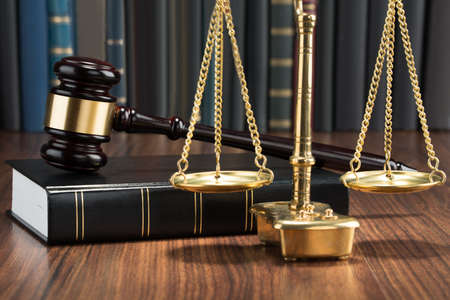 criminals: Wooden Gavel On Book With Golden Scale On Table
