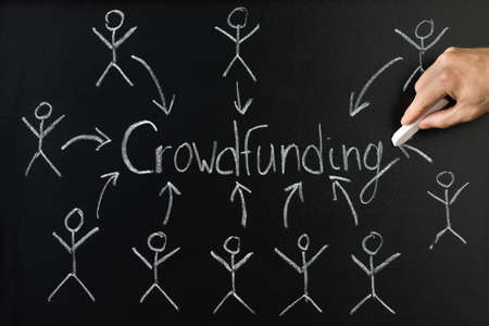 college fund savings: Close-up Of Person Drawing Arrow Direction With Crowd Funding Text On Blackboard Stock Photo