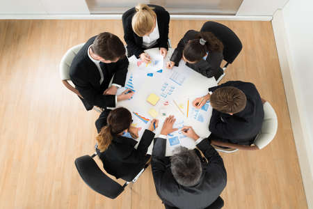 High Angle View Of Businesspeople Discussing Graph In Office photo