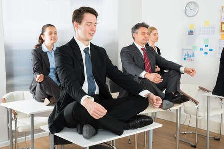 woman meditating: Meditando empresarios que se sientan en el escritorio con las piernas cruzadas en oficina