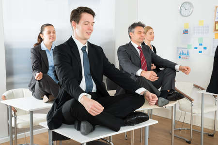 positions: Meditating Businesspeople Sitting On Desk With Their Legs Crossed In Office Stock Photo