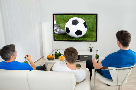 Rear View Of Three Men Sitting On Couch Watching Football Match On Television