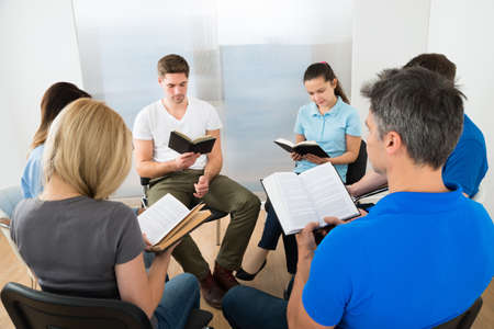 bible reading: Group Of Multiethnic Friends Reading Bible Together Stock Photo
