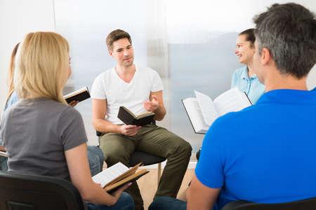 leer biblia: Hombre explicar a sus amigos de la Escritura Foto de archivo