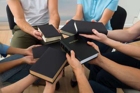 familia orando: Primer plano de personas que se sientan junto Holding Santa Biblia