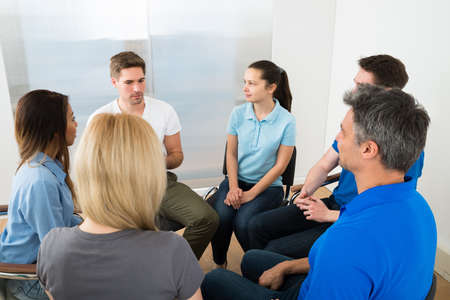 personas escuchando: La gente escuchando a un hombre gesticula con las manos