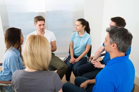 Mensen luisteren naar een man gebaren met de handen