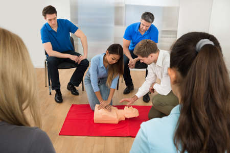 chest compression: Instructor Demonstrating Cpr Chest Compression On A Dummy