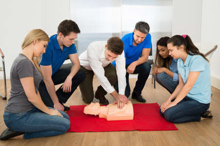 First Aid Instructor Showing Resuscitation Technique On Dummy 스톡 콘텐츠