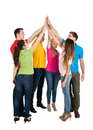 high spirits: Happy Multiethnic Friends High Five For Their Teamwork Over White Background Stock Photo
