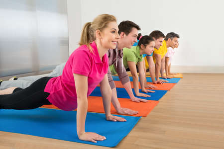 push people: Multiethnic Group Of People Doing Push Ups On Exercise Mat