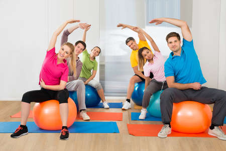 ball stretching: Group Of People Sitting On Pilates Ball Stretching