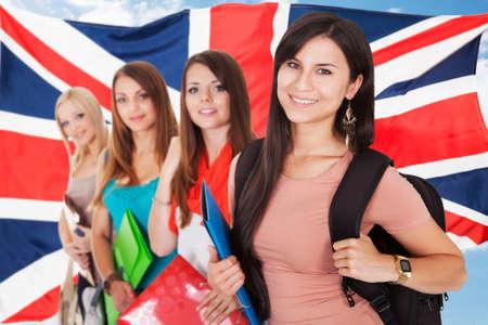 languages: Grupo de estudiantes universitarios feliz se coloca delante de la bandera británica Foto de archivo