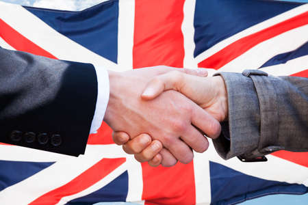 british people: Close-up Of Two Businesspeople Shaking Hands In Front Of British Flag