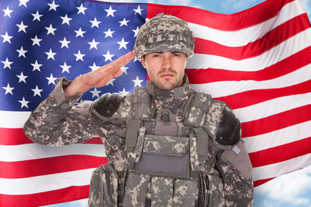 Retrato del soldado que saluda delante de la bandera americana