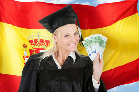 Female Graduate Student Holding Money In Front Of Spanish Flag photo
