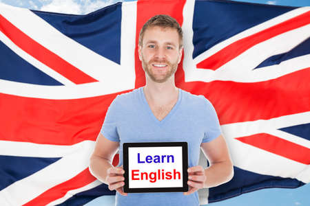 english text: Young Man In Front Of British Flag Holding Digital Tablet With Learn English Text