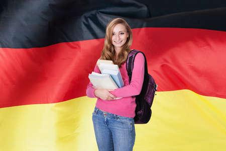 Jonge vrouwelijke student die boeken voor Duitse Vlag