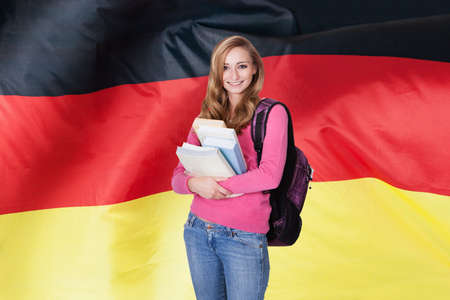 Young Female Student Holding Books In Front Of German Flag