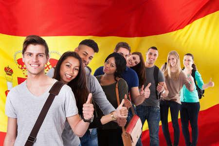 languages: Grupo de feliz estudiantes étnicos multi coloca delante del bandera de España, mostrando el pulgar
