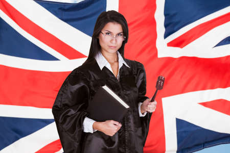 Portrait Of Female Judge With Book And Gavel Standing In Front Of Uk Flag photo