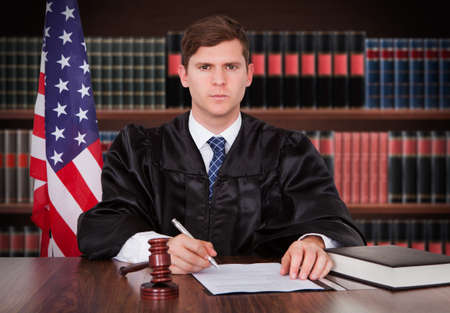 judges: Portrait Of Young Male Judge Sitting In Courtroom Stock Photo