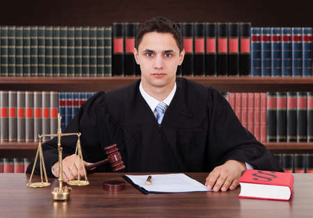 criminal lawyer: Portrait Of Young Male Judge Striking Gavel In Courtroom Stock Photo