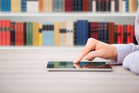 library: Primer plano de la mano de la mujer que usa la tablilla digital