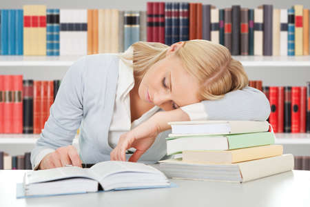 Tired Female Student Sleeping On The Books In The Library photo