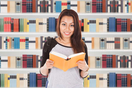 university choice: Portrait Of Female Student In Library Reading Book