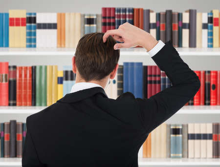 contemplated: Rear View Of Man In A Suit Scratching His Head In Library