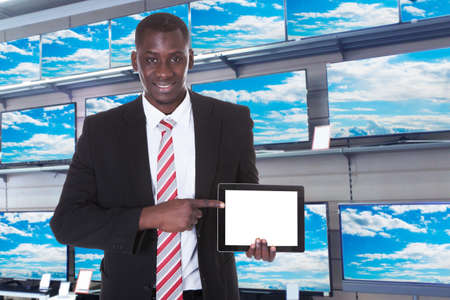 african businessman: Young African Businessman Pointing At Digital Tablet In Store Stock Photo