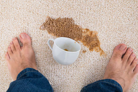 carpet flooring: Close-up Of A Persons Feet Standing Near Coffee Spilled On Carpet