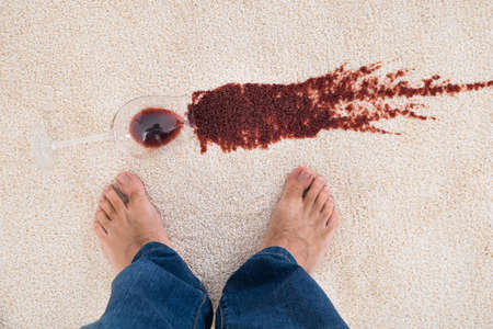 wine stains: Close-up Of A Persons Feet Standing Near Red Wine Spilled On Carpet