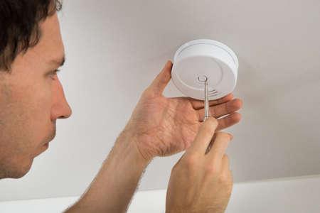 incendio casa: Primer De Electricista con destornillador Reparación Sensor Fuego Foto de archivo
