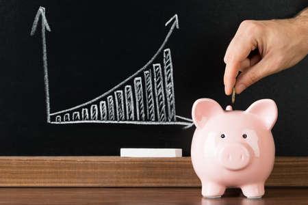prosperidad: Poniendo la mano una moneda en la bater�a guarra delante de la pizarra que muestra el gr�fico