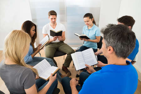 bible: Group Of Multiethnic Friends Reading Bible Together Stock Photo