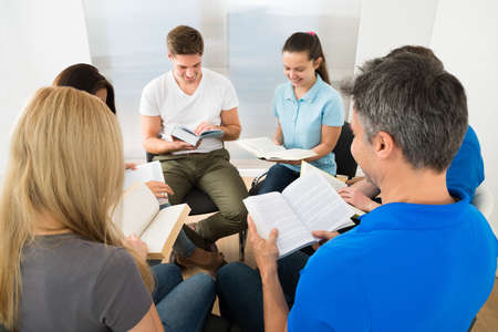 book club: Group Of People Sitting Together Reading Books Stock Photo