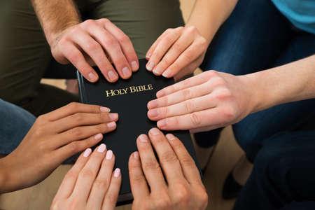 mujeres orando: Grupo de personas mantiene la Biblia y orando juntos Foto de archivo