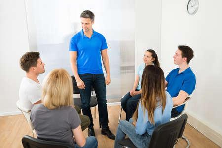 terapia de grupo: Grupo de personas Mirando a hombre Explicando