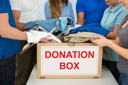 vagabundos: Primer plano de personas que pone la ropa interior de la casilla de donación