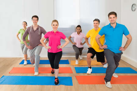 active people: Group Of Happy Multiethnic People Doing Exercise In Gym