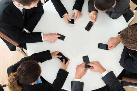 liggande: Grupp av affärsmän använder mobiltelefon sitter vid bordet