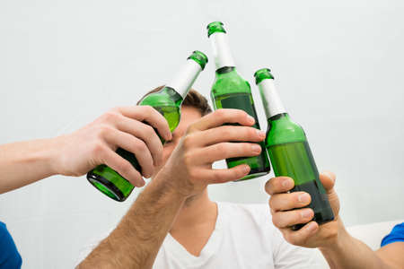 hand holding bottle: Close-up Of Mens Hand Toasting Beer Bottles
