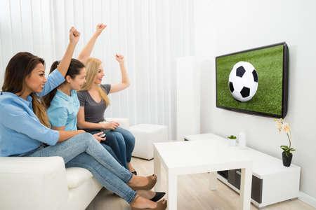 cerillos: Mujeres multi�tnica que se sienta en el sof� que ve V�tores Partido de F�tbol Foto de archivo