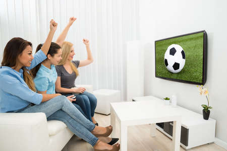 Multiethnic Women Sitting On Couch Cheering Watching Football Match