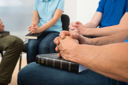 Close-up Of People Praying With Holy Bible Stock Photo