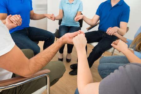 terapia de grupo: Grupo de personas que juegan a manos de explotaci�n Foto de archivo
