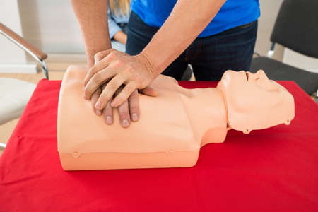 reanimate: First Aid Instructor Showing Resuscitation Technique On Dummy Stock Photo